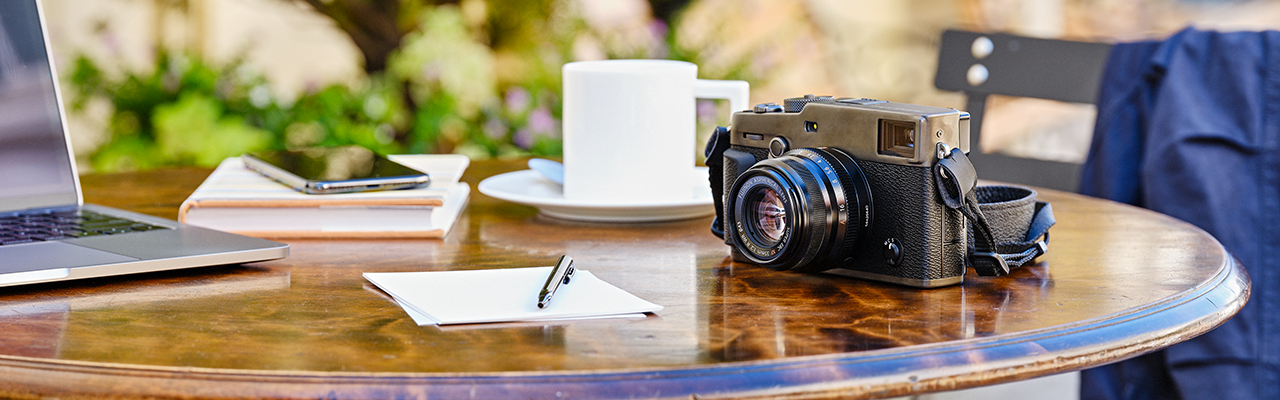 [photo] A Fujifilm digital camera on a garden table with other writing materials outside