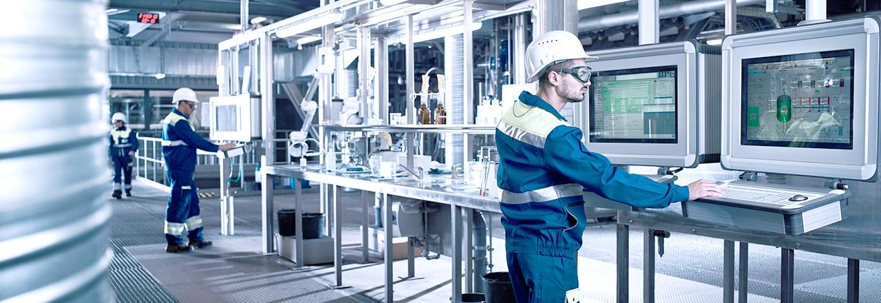 [photo] Man wearing glasses, hardhat, and heavy clothing, standing in front of two large computer screens in a manufacturing facility