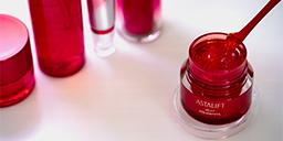 [photo] An opened jar Astalift Jelly Aquarysta with a stirrer surrounded by other beauty products